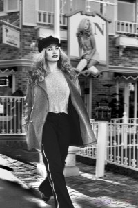 Black and white portfolio photograph of a blonde model walking next to a marquee featuring herself. Model photographer in L.A.