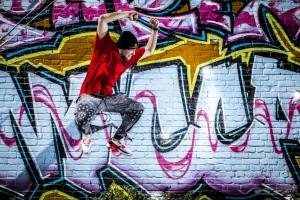 Lifestyle photography of choreographer Kai McMinn extreme jump, wearing street fashion in Venice California