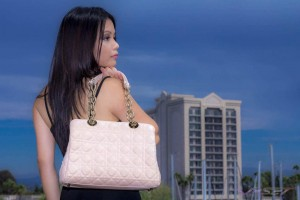 Outdoor fashion shot of model Vanessa sporting a peach Christian Dior handbag with gold hardware over her shoulder in Marina Del Rey California